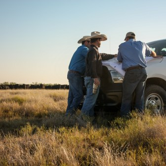 Michael Wilson, NRCS Snyder resource team leader, discusses a specific pasture in the Griffins' NRCS conservation plan with Tom and Dan on their family ranch.