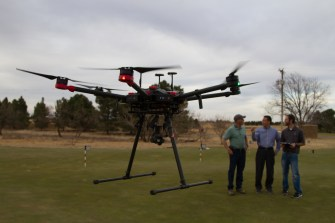 [Left to Right] Rodnie Bermea, Wenxuan Guo Ph. D., and Joey Young Ph. D., discuss plans for the turfgrass research as the drone, equip with sensors designed to detect drough stress, warms up.