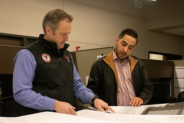 Dr. Guy Loneragan looks at the construction plan for the School of Veterinary Medicine with Project Manager Redha Gheraba