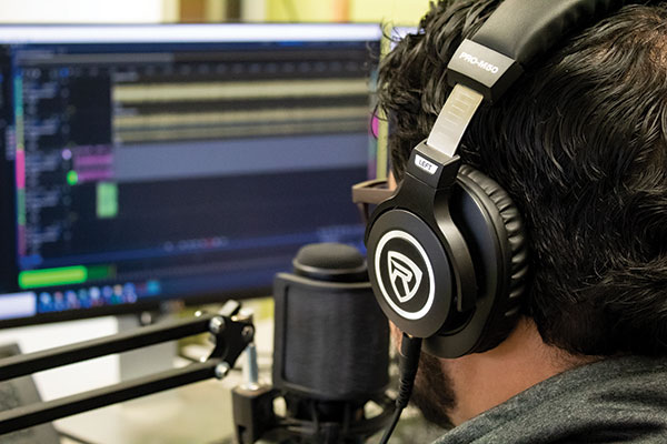 Photo of Vikram Baliga recording an episode of his podcast.