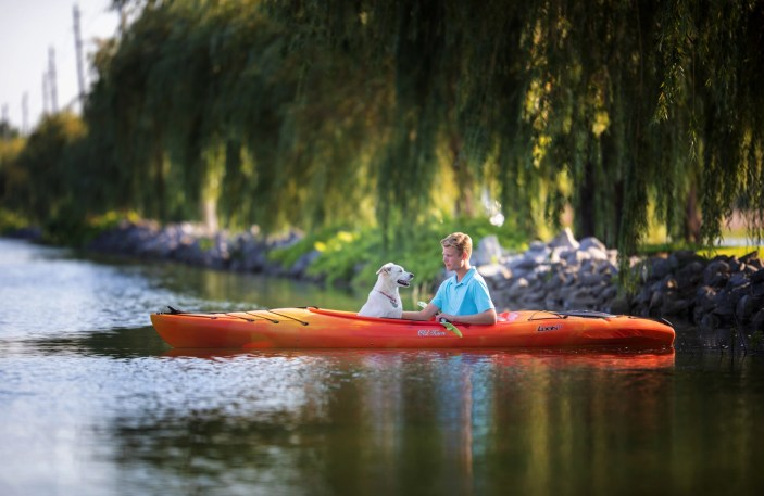 young man on old town kayak with dog
