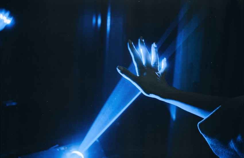 photo of person s hand with blue light