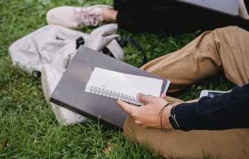 crop unrecognizable students studying together on grassy meadow
