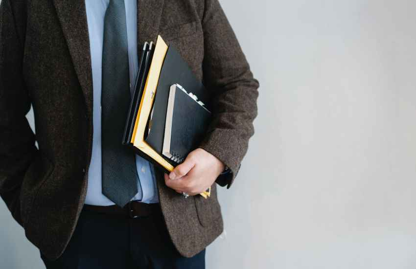 crop unrecognizable office worker standing with papers in hand