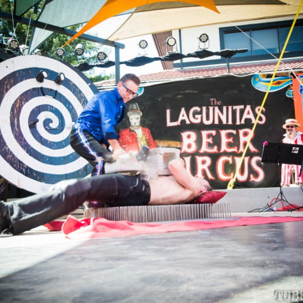 Molotov uses a sledgehammer to break a cinderblock laying on top of a performer laying on a bed of nails. Photo Melissa Uroff