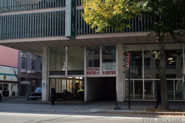 A businessman crosses in front of a parking garage on 8th Street. Photo M.Hershenow. 2014.
