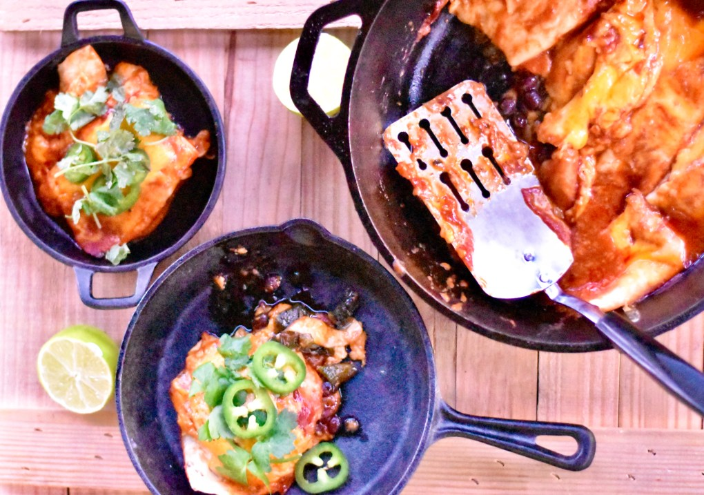 An overhead shot of a camping meal, including three cast iron pans,  one with a very cheesy enchilada plate hot off the grill on a wood background. The other two pans hold smaller portions of the oozing cheesy enchilada.