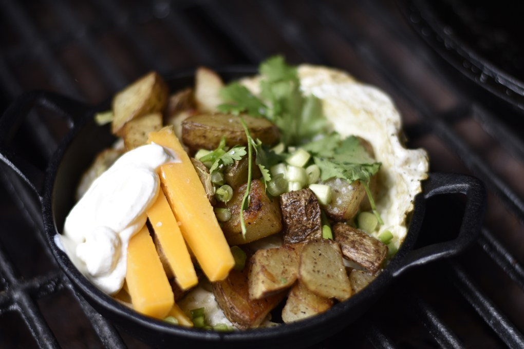 A cast iron dish with a potato, cheddar cheese, sour cream and fried egg all mixed in together with a garnish of green onions.
