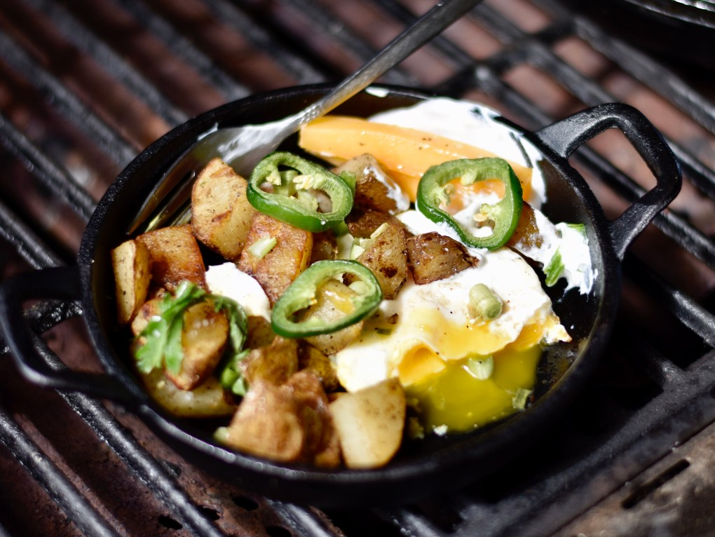 A cast iron dish with a potato, cheddar cheese, sour cream and fried egg all mixed in together with a garnish of green onions. This time the egg is oozing over the potatoes.