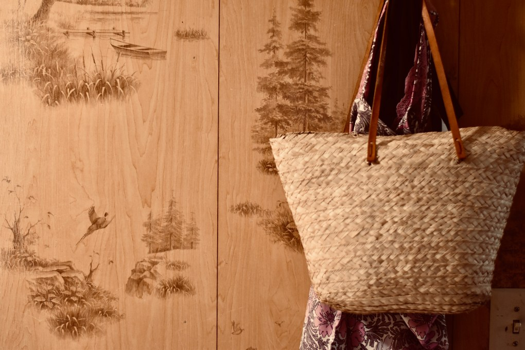 Old panelling on the cabin walls showing the faux wood covered in idyllic scenes of ducks, trees.In front, a traveling basket bag hangs with a delicate garment.