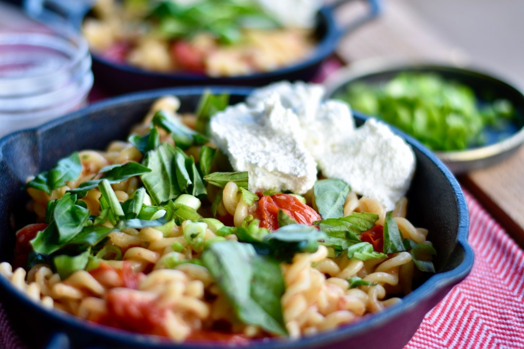 A pasta dish with spiral pasta and cherry tomatoes, a large dollop of ricotta cheese and basil and green onion garnish.