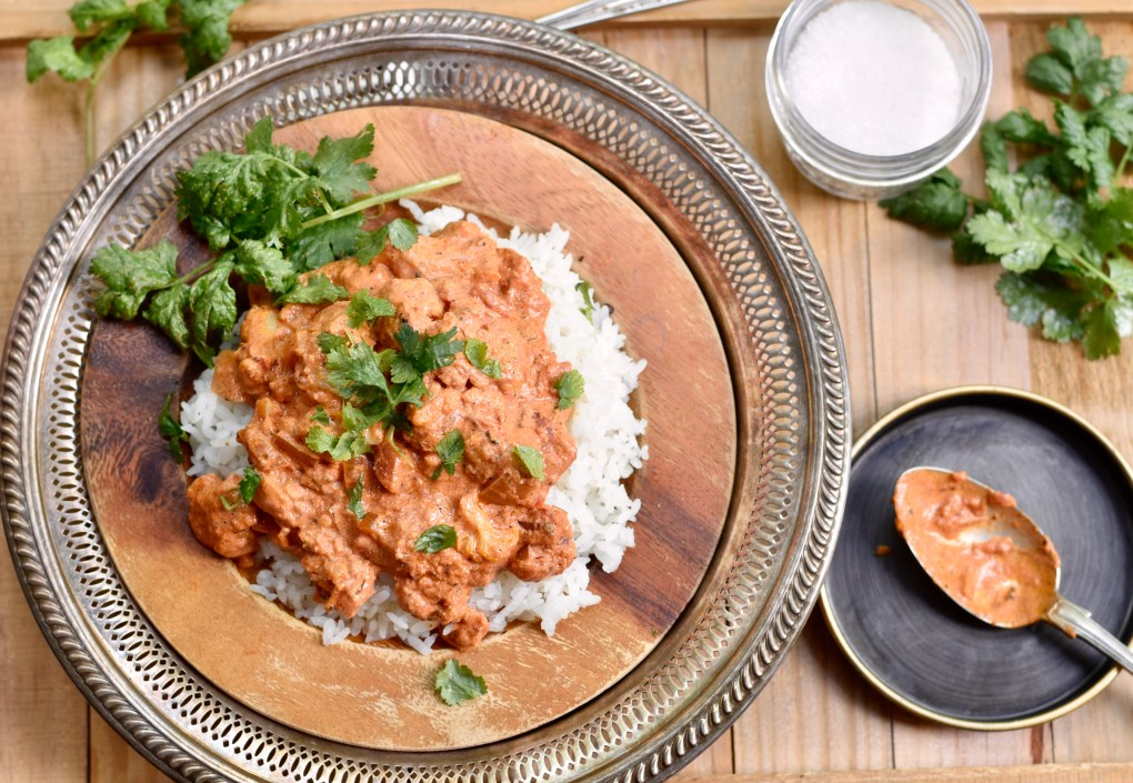 A large ornate plate, shot from overhead, with a heaping plate of vegetarian cauliflower tikka masala, and a bit of cilantro placed on top.