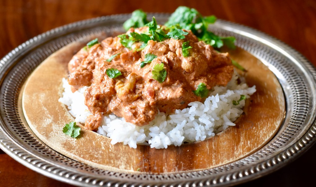 An ornate plate with a heaping portion of vegetarian cauliflower tikka masala, and cilantro garnish, served over rice.