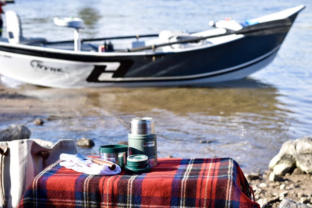 A thermos on a plaid picnic blanket in front of a fishing boat