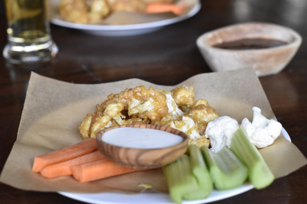 A meal of beer battered cauliflower bites with celery, carrots and ranch, in front of a nice glass of lager