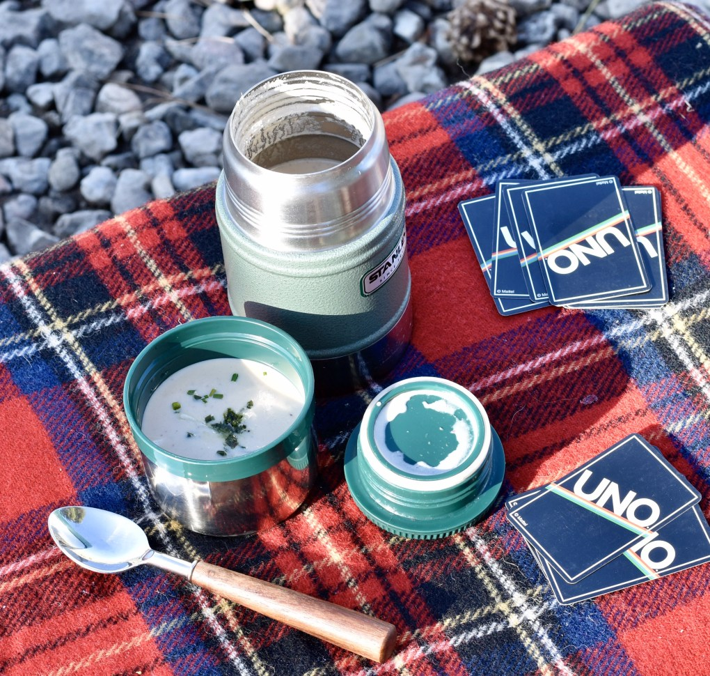 Picture of a thermos with soup on a plaid picnic blanket