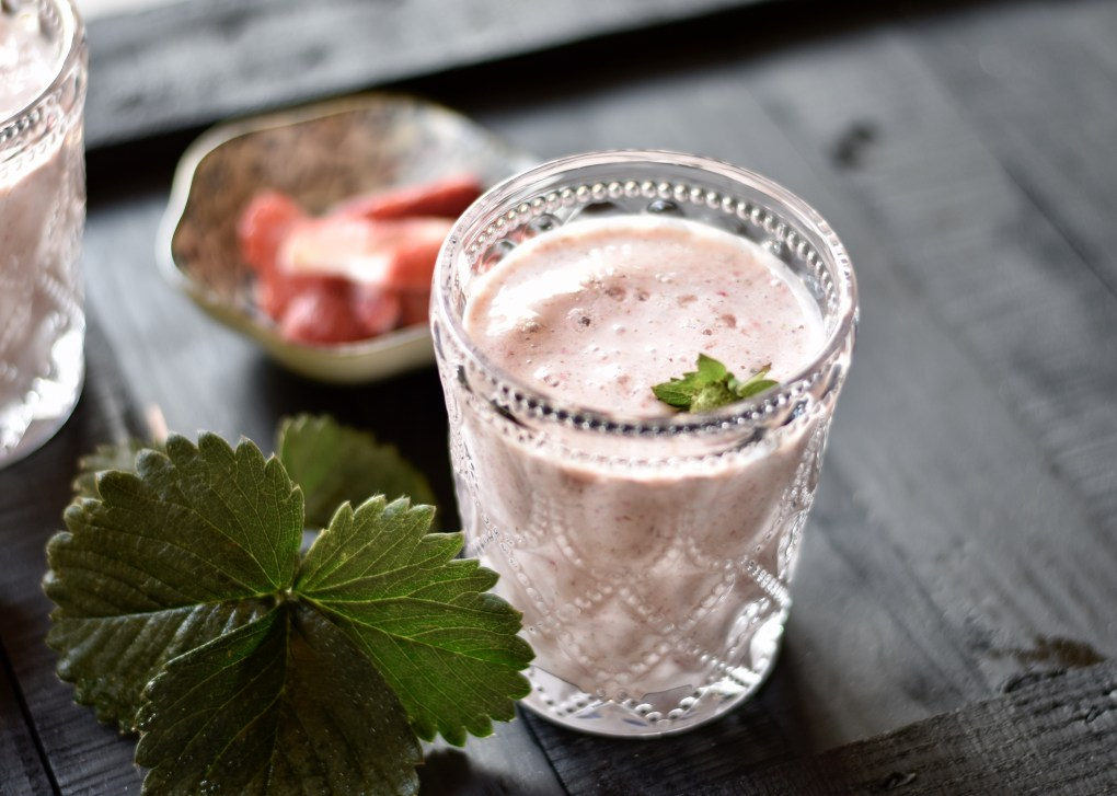 Close up of a home-grown strawberry made smoothie with strawberry leaves