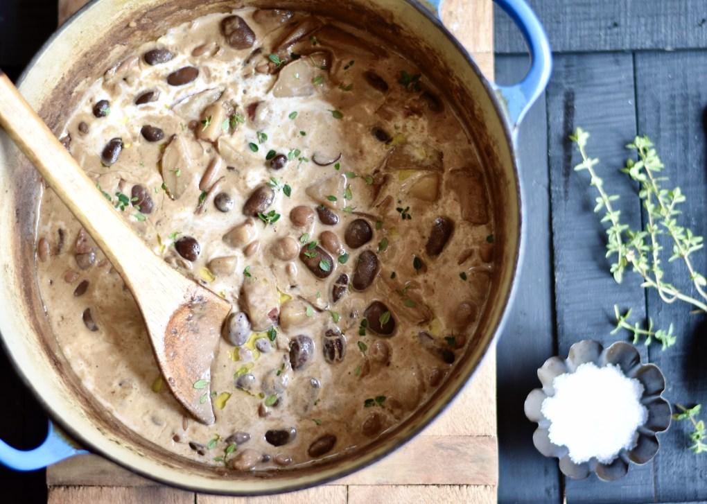 A closeup of a hearty, creamy potato and bean soup with loose thyme.