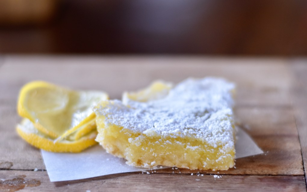 Extreme close up of a lemon bar with a lemon garnish.