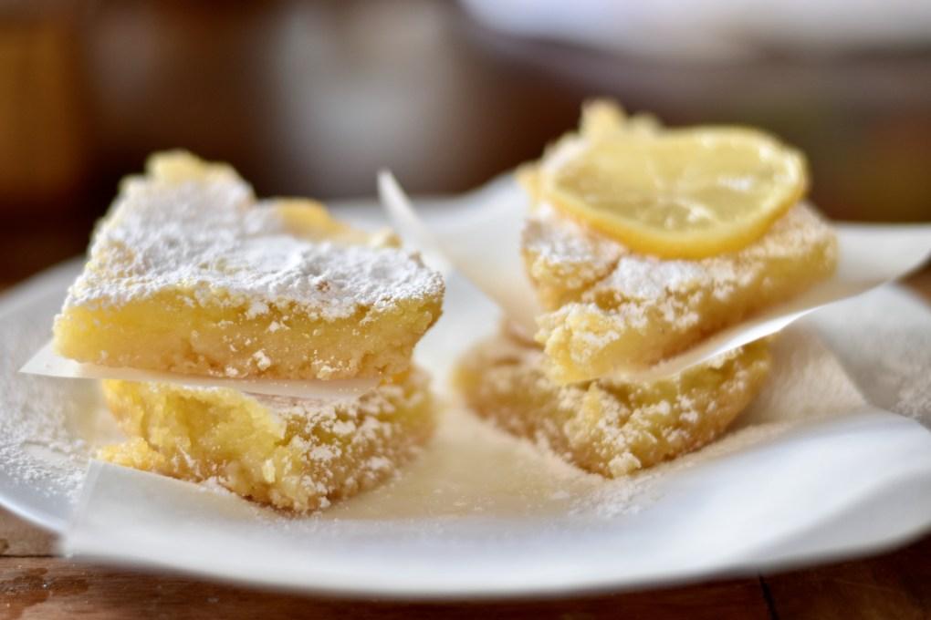 Close up of four yummy lemon bars.