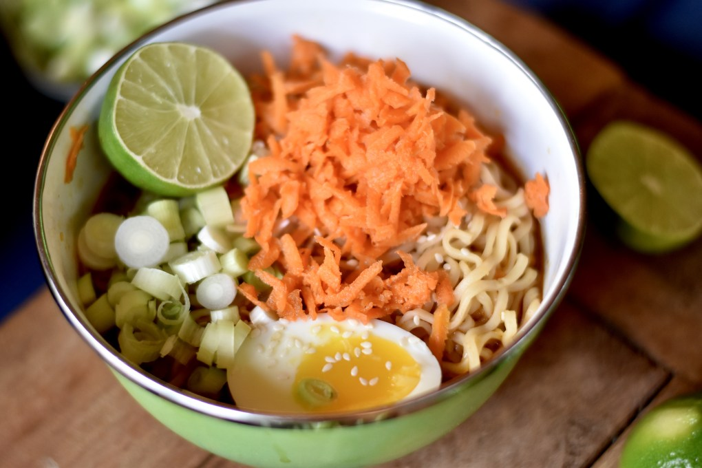 A close up of a bowl of ramen with shredded carrots, a soft boiled egg, scallions and a lime.