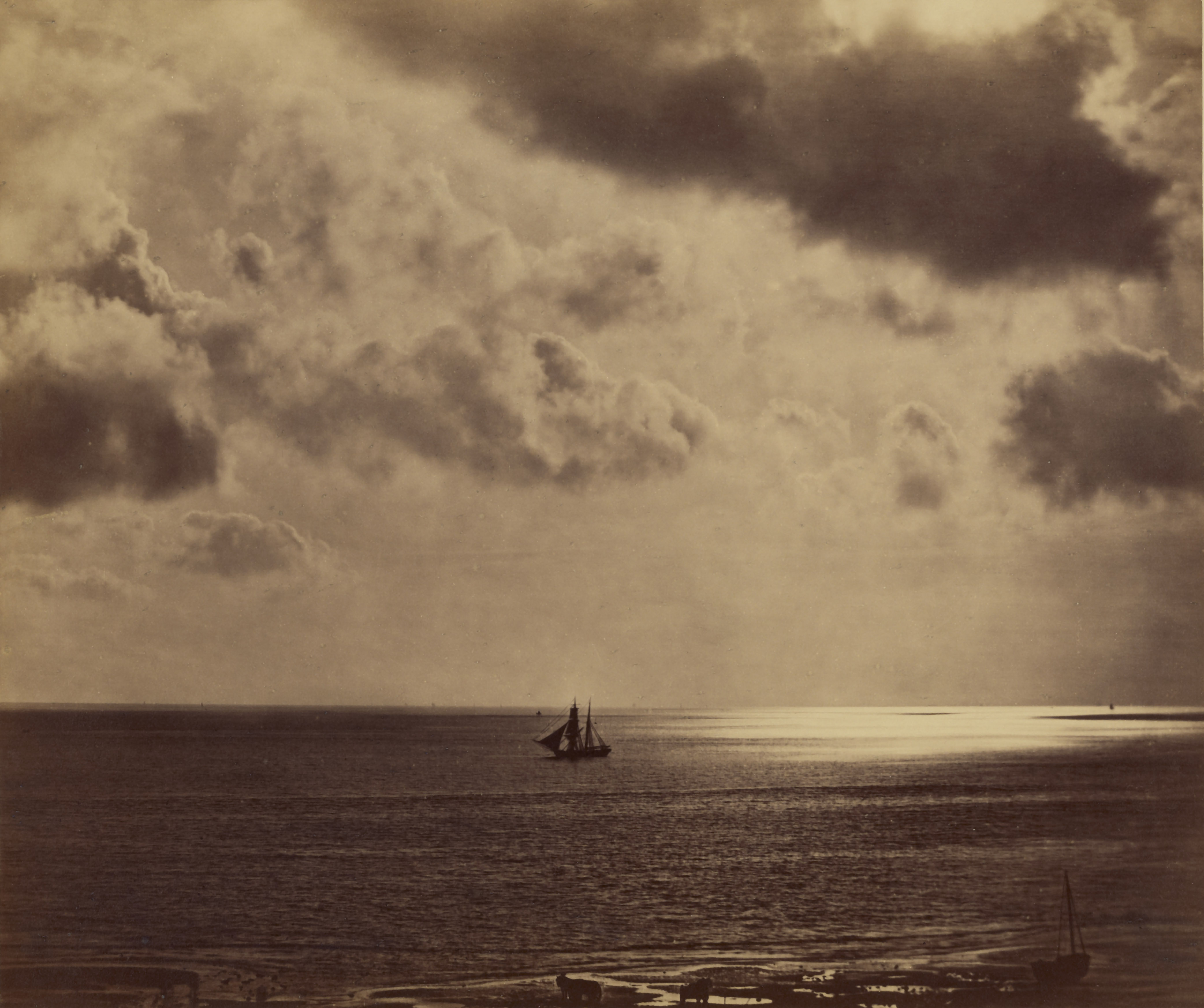 A picture of a small sail boat on the mediteranian sea. The detail in the shore and sea can be clearly made out, dispite the sky being much brighter. In the right side of the image, the sun glares on the warm water, a bright sunny patch over exposing the camera.