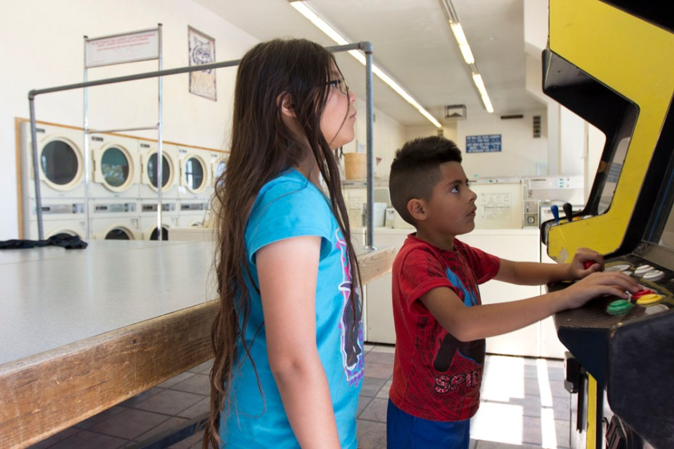 Video games at the Fair Wash Laundry on 6th Street in Tucson kept Yesenia and Frank Ruiz entertained as their parents dried and folded on Friday.