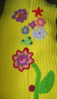 One of the lamppost sleeves with some of her crocheted flowers on it