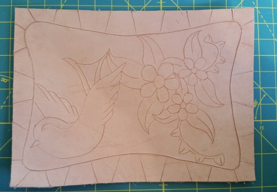 First I traced the design onto the leather with a dull pencil through the paper, just to get grooves, and then used a swivel knife to cut along the lines