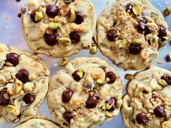 Dark Chocolate, Pistachio, & Toffee cookies on a baking sheet
