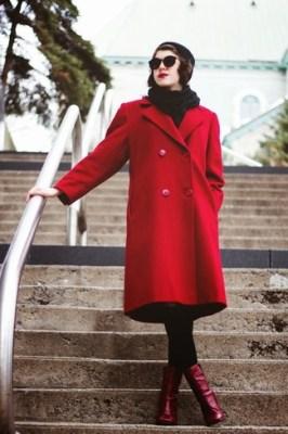 modelo veste casaco comprido vermelho, calça preta e botinha vermelha.
