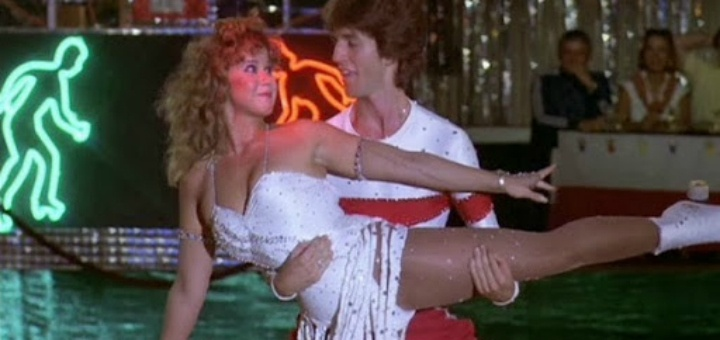A still from the movie Roller Boogie; couple is skating, man is holding and lifting woman's thigh, her arms are outstretched, and they are gazing at each other.