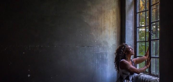 Black woman in a barren darkened room, looking out of a window