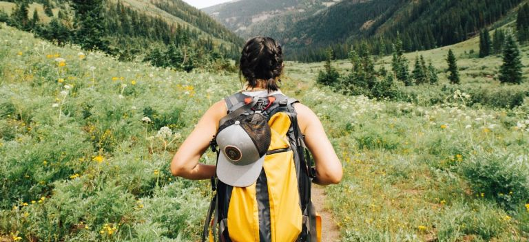 The back of a woman, wearing a yellow backpack, walking in nature towards mountains