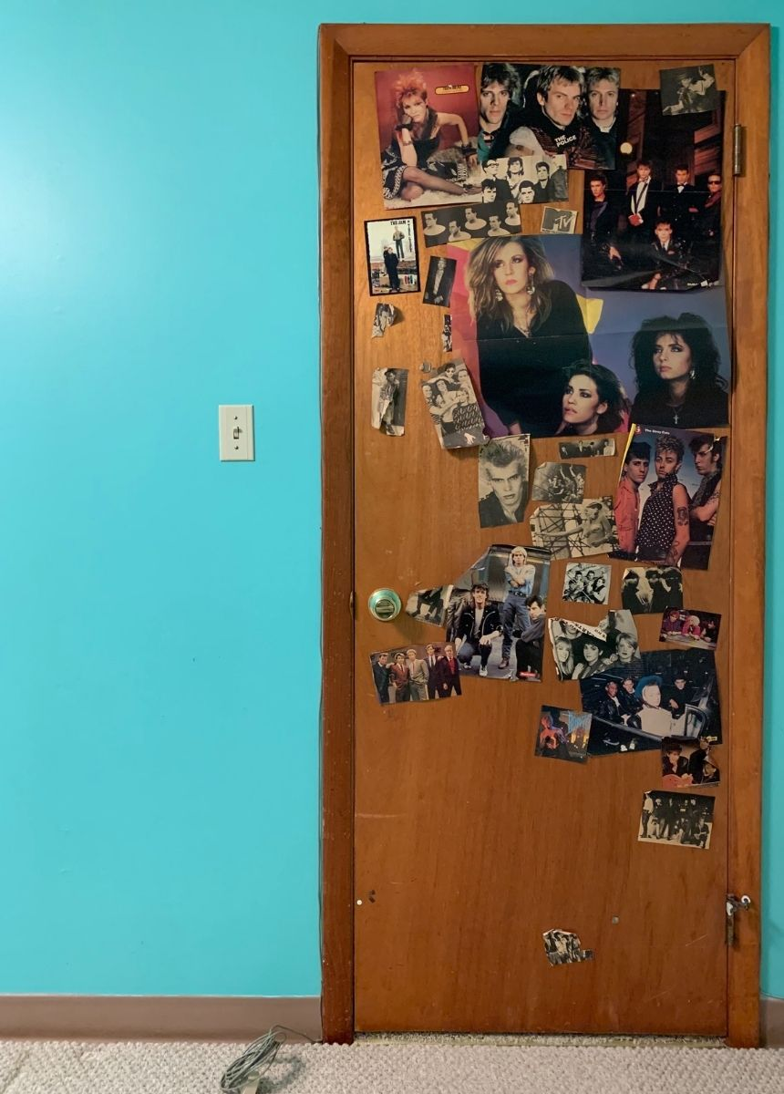 The door of the author's childhood bedroom, covered in 1980s magazine clippings of pop stars