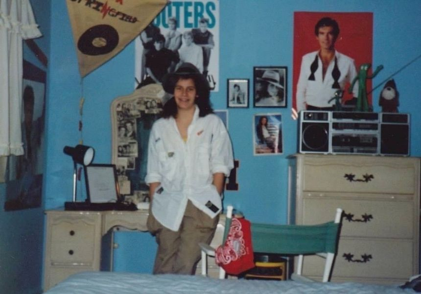 The author as a teenage in her childhood bedroom, smiling at the camera, with a poster of Remington Steele on the wall behind her
