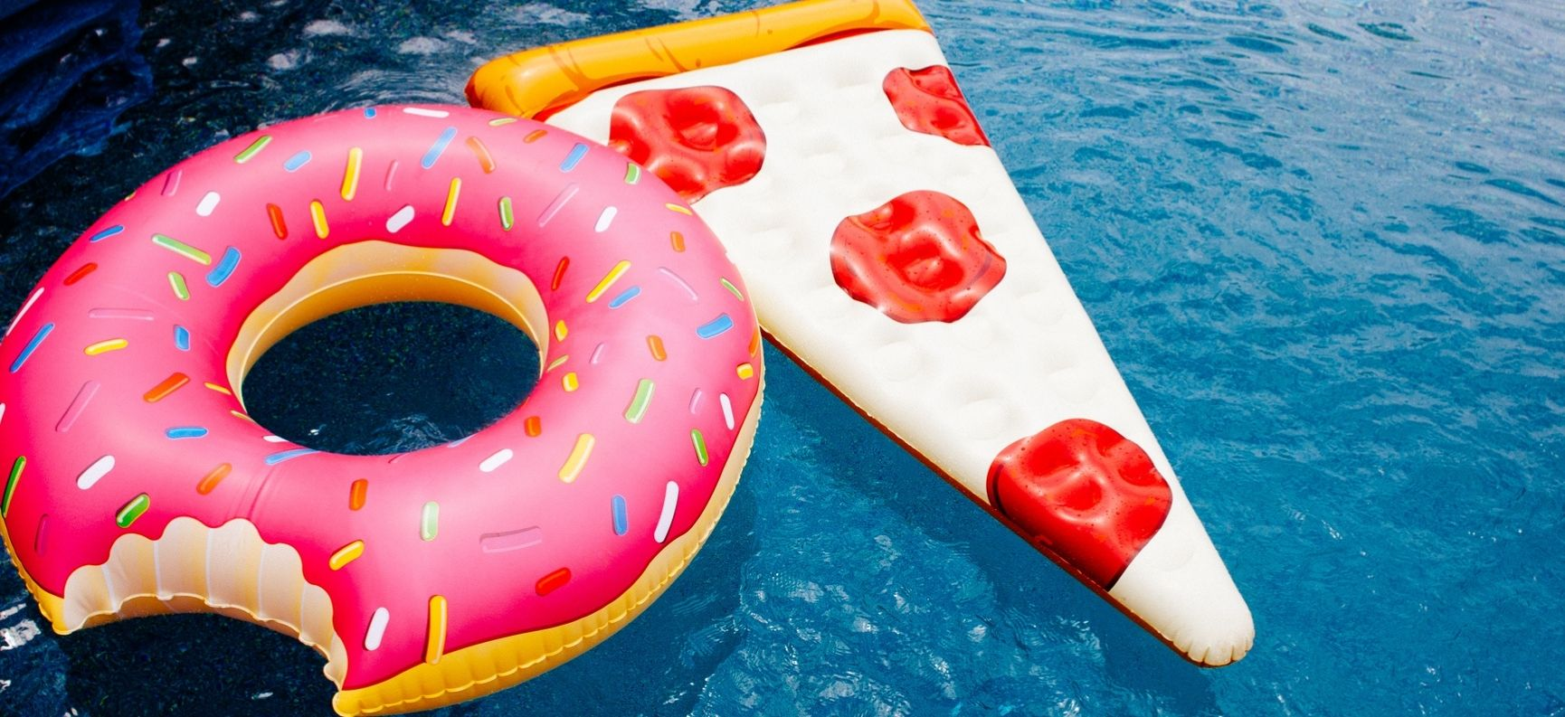 Two floats in a swimming pool, one shaped like a donut with a bite taken out of it, one like a pizza slice, very close together
