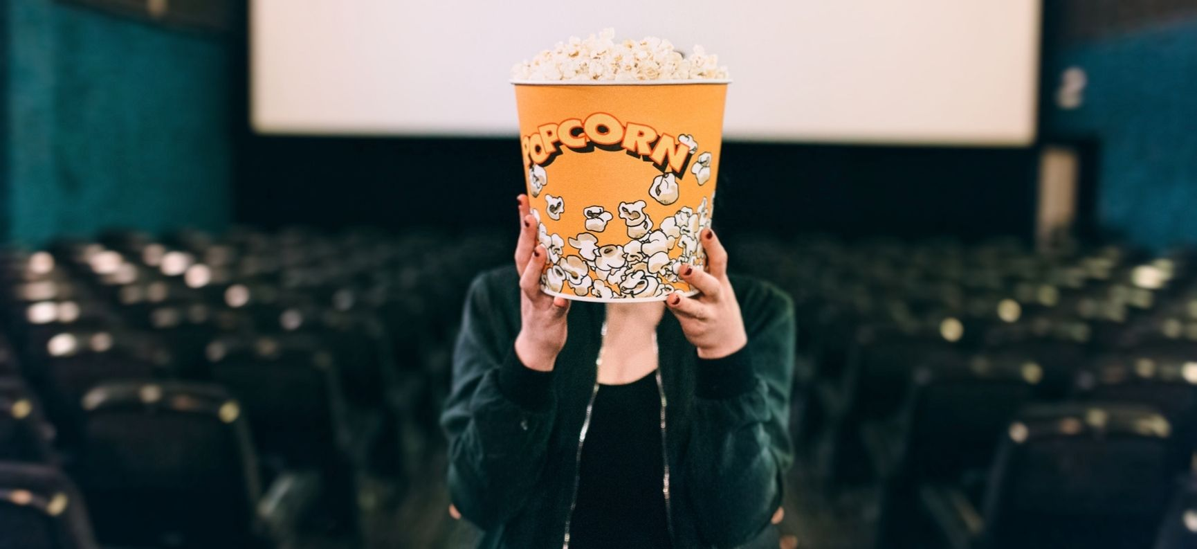 Woman holding popcorn container in front of her face in a movie theater
