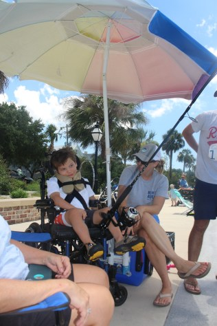 Charlie has his fishing rod mounted to his wheelchair and enjoyed fishing with his parents.