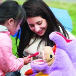 10/04/2015 - Medford/Somerville, Mass. - A member of the Smile Squad, part of the Tufts School of Dental Medicine, uses a specially made stuffed animal to demonstrate to a child how to brush at Community Day on Oct. 4, 2015. (Evan Sayles for Tufts University)