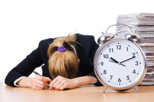 woman with head on desk with alarm clock