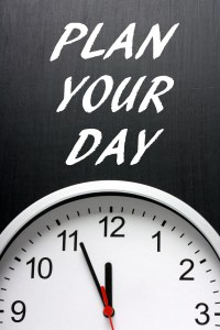 The phrase Plan Your Day in white text on a blackboard avove a modern wall clock