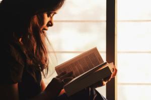 woman reading a book beside a window