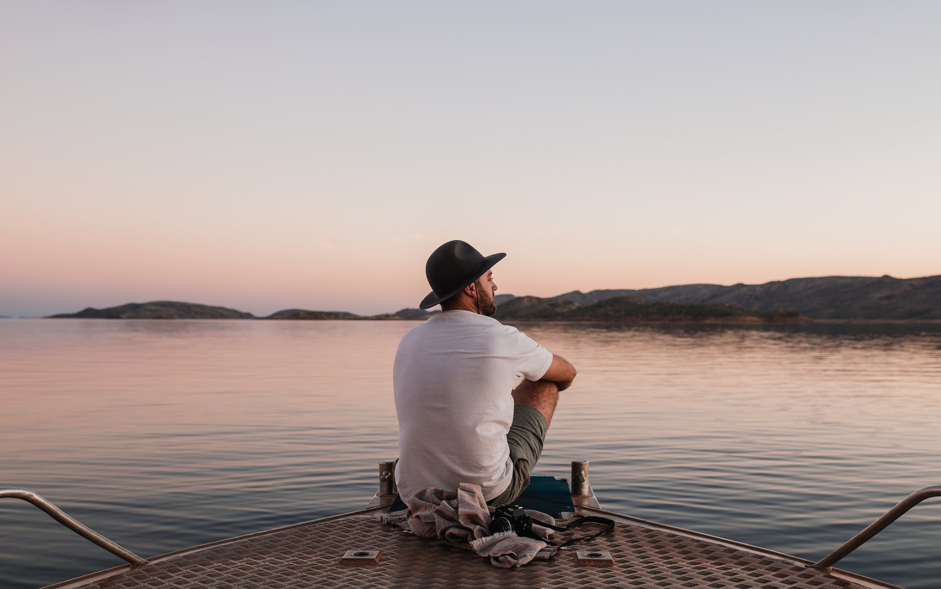 anonymous male sitting on boat above water