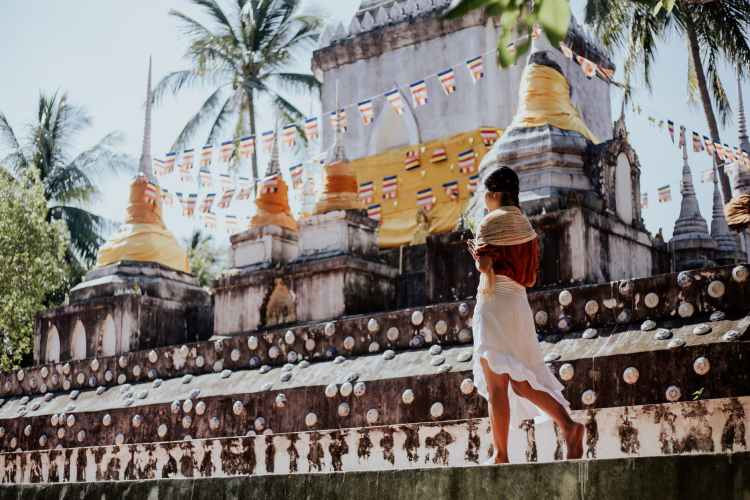 woman in white dress standing near gold temple
