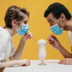 couple wearing face mask drinking milkshake