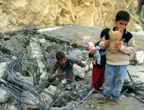 PALESTINIAN CHILDREN WALK THROUGH REMAINS OF DEMOLISHED HOUSE IN ISAWIYAH