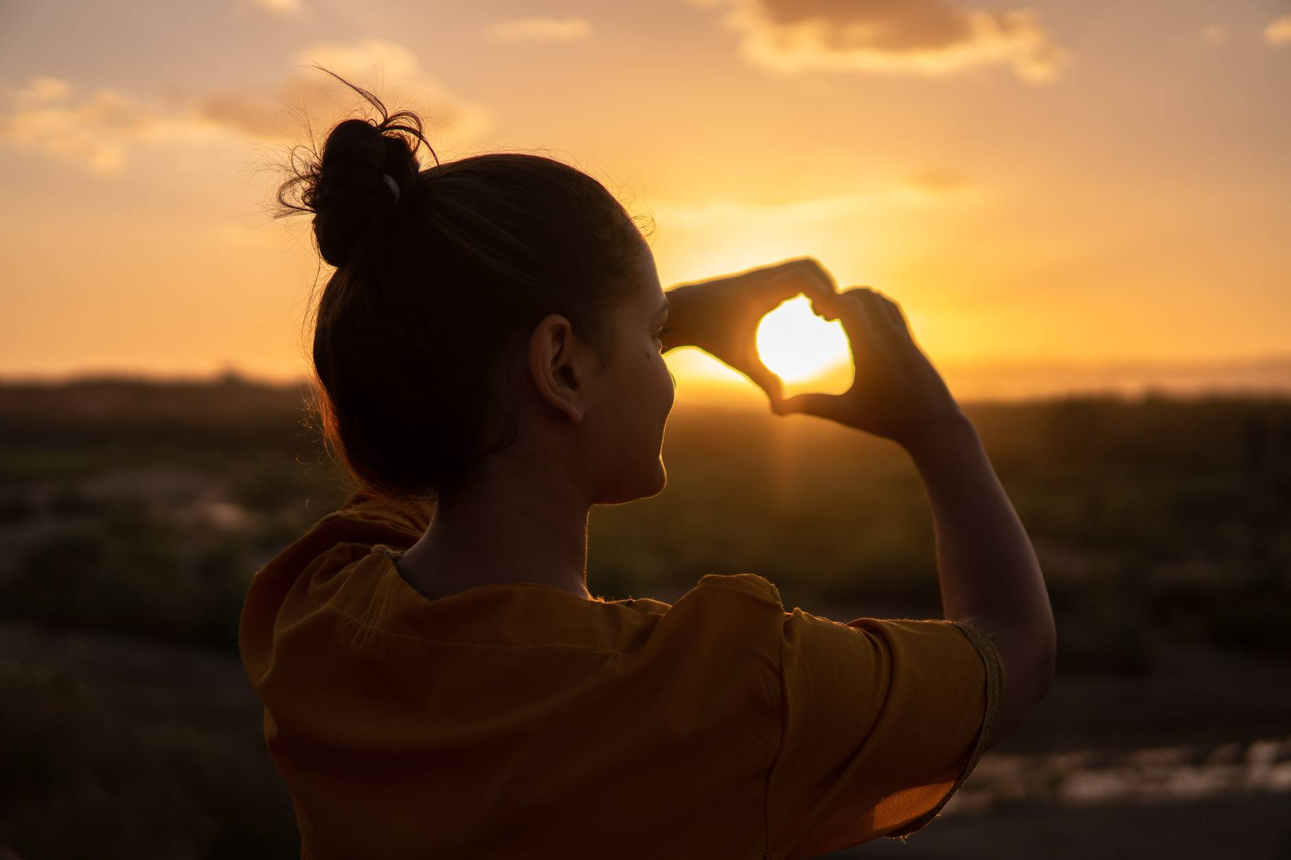 woman watching sunset doing hand heart sign. Watching the sunset can be part of routine self-care.