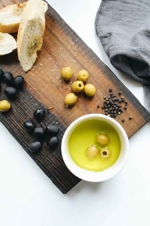 photo of ceramic bowl with olive oil on top of wooden chopping board