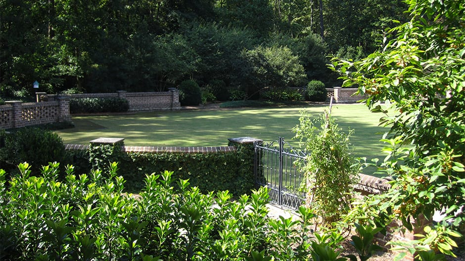 view across tennis lawn at an Atlanta residence. landscape designed by Tunnell and Tunnell Landscape Architecture